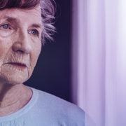 Senhora com Alzheimer olhando pela janela