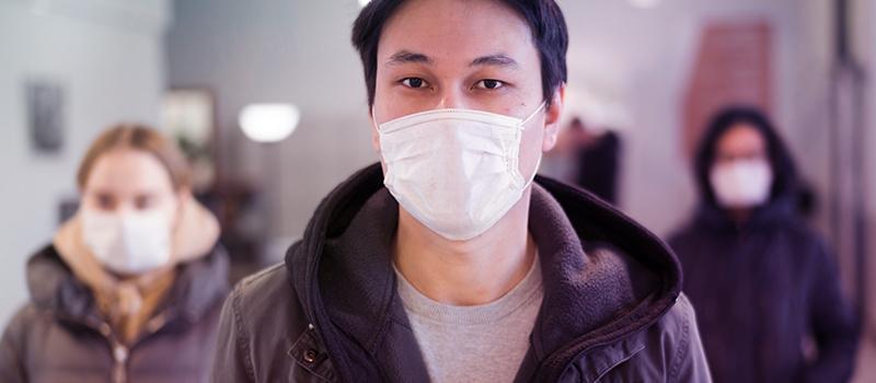 Homem oriental usando máscara de proteção na rua com outras pessoas andando por trás dele